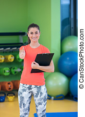 Portrait of smiling female fitness instructor writing in clipboard while standing in gym