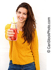 smiling female holding a glass of juice