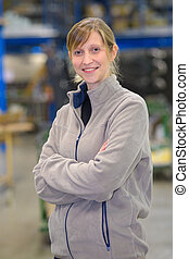 portrait of smiling female manager with arms crossed in warehouse