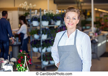 Portrait Of Smiling Female Salesperson In Flower Shop
