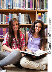 Portrait of smiling female students with a book