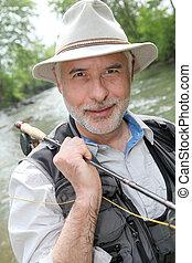Portrait of smiling fisherman on riverside