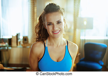 Portrait of smiling fit woman in sport clothes at modern home