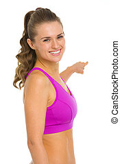 Portrait of smiling fitness young woman pointing back on copy space
