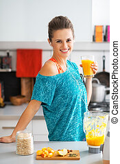 Portrait of smiling fitness young woman with glass of...