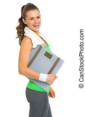 Portrait of smiling fitness young woman with scales