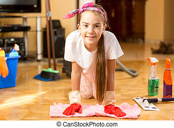 Portrait of smiling girl cleaning wooden floor with rag -...