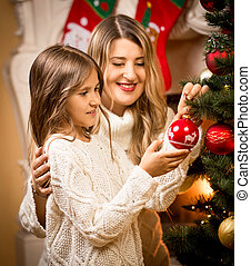 smiling girl helping mother to decorate Christmas tree