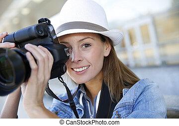 Portrait of smiling girl holding photo camera