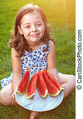 Portrait of smiling girl holding watermelon slices in the garden