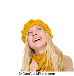 Portrait of smiling girl in autumn clothes looking up on copy space