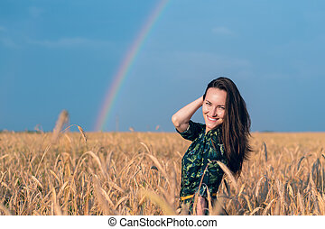 Portrait of smiling girl in wheat field with Golden spikelets on rainbow background