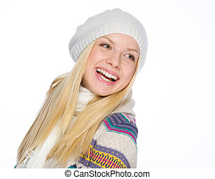 Portrait of smiling girl in winter clothes looking on copy space