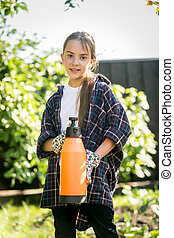 Portrait of smiling girl posing at garden with spray
