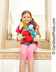 smiling girl posing with cleansers in bottles at bathroom