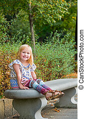 Portrait of smiling girl sitting on bench in city park