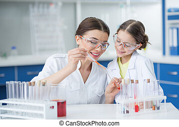 portrait of smiling girl student watching scientist teacher making experiment in lab