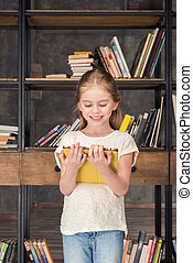 portrait of smiling girl using digital tablet in library