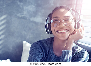 Portrait of smiling girl with headphones listening to music while sitting on sofa at home