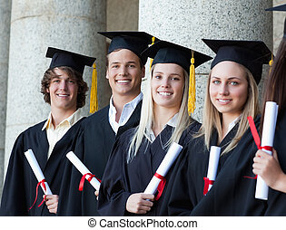 Portrait of smiling graduates posing in single line with...
