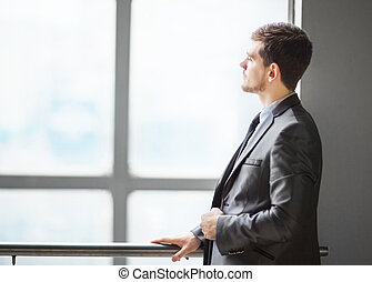 Portrait of smiling handsome businessman looking out the window