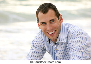 A handsome smiling man is outside in dress shirt looking at viewer