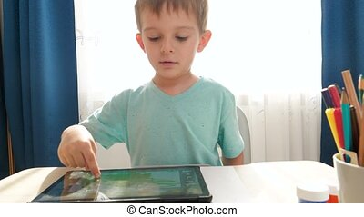 Portrait of smiling happy boy playing on digital tablet computer after studying and doing homework at home