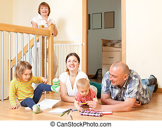 Portrait of smiling happy three generations family with two little children at home in living room together