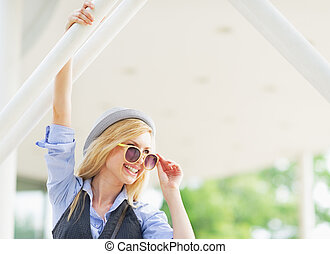 Portrait of smiling hipster girl in sunglasses in the city looking on copy space