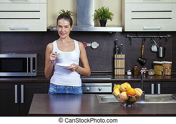 Portrait of smiling housewife in kitchen at home