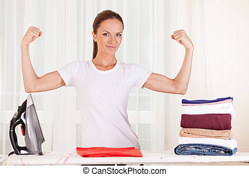 Portrait of smiling housewife ironing clothes. waist up housewife standing and showing muscles
