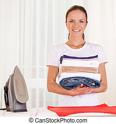 Portrait of smiling housewife ironing clothes. waist up housewife standing in bedroom and holding clothes