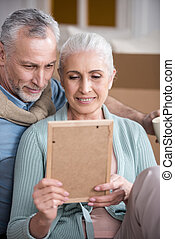portrait of smiling husband and wife looking at photo frame together