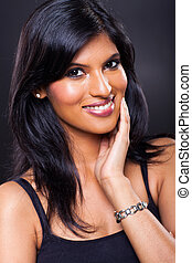smiling indian woman posing on black background