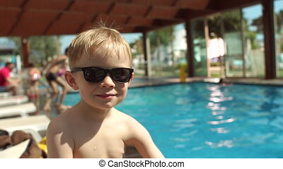 Portrait of smiling little boy with sunglasses on pool background, slow motion.