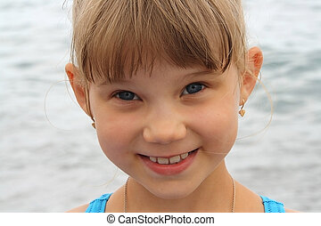 portrait of smiling little funny blonde girl