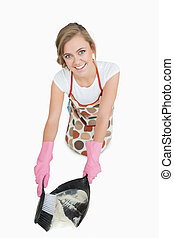 Portrait of smiling maid using brush and dust pan over white...
