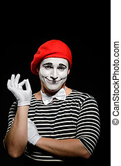 Portrait of smiling male mime on black