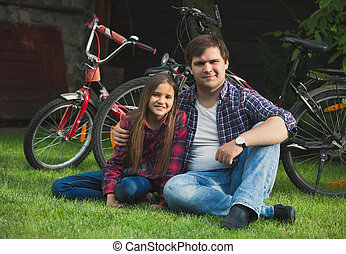 Portrait of smiling man and girl relaxing on grass after riding bicycles