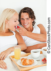 Portrait of smiling man giving a strawberry to his girlfriend
