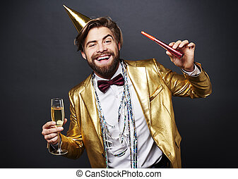 Portrait of smiling man holding champagne flute and party...