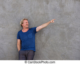 smiling man leaning against a wall and pointing at copy space
