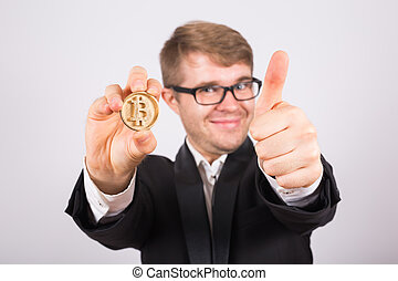 Portrait of smiling man showing thumbs up and holding bitcoin