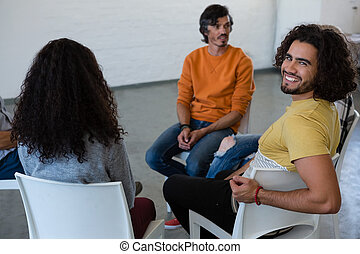 Portrait of smiling man sitting with friends