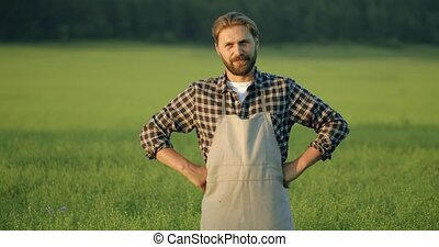 Portrait of smiling man standing among agricultural lands - ...