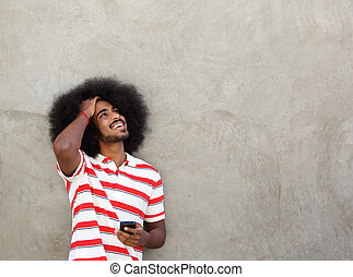 smiling man standing with hand to hair and cellphone