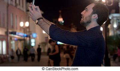 Portrait of smiling man taking photo of himself