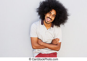 smiling man with afro standing with arms crossed