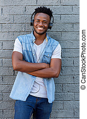 smiling man with headphones standing with arms crossed