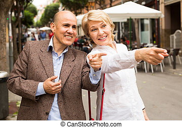 walking and pointing - Portrait of smiling mature couple ...